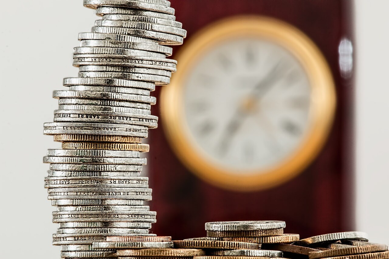 stack of coins with blurry clock in background