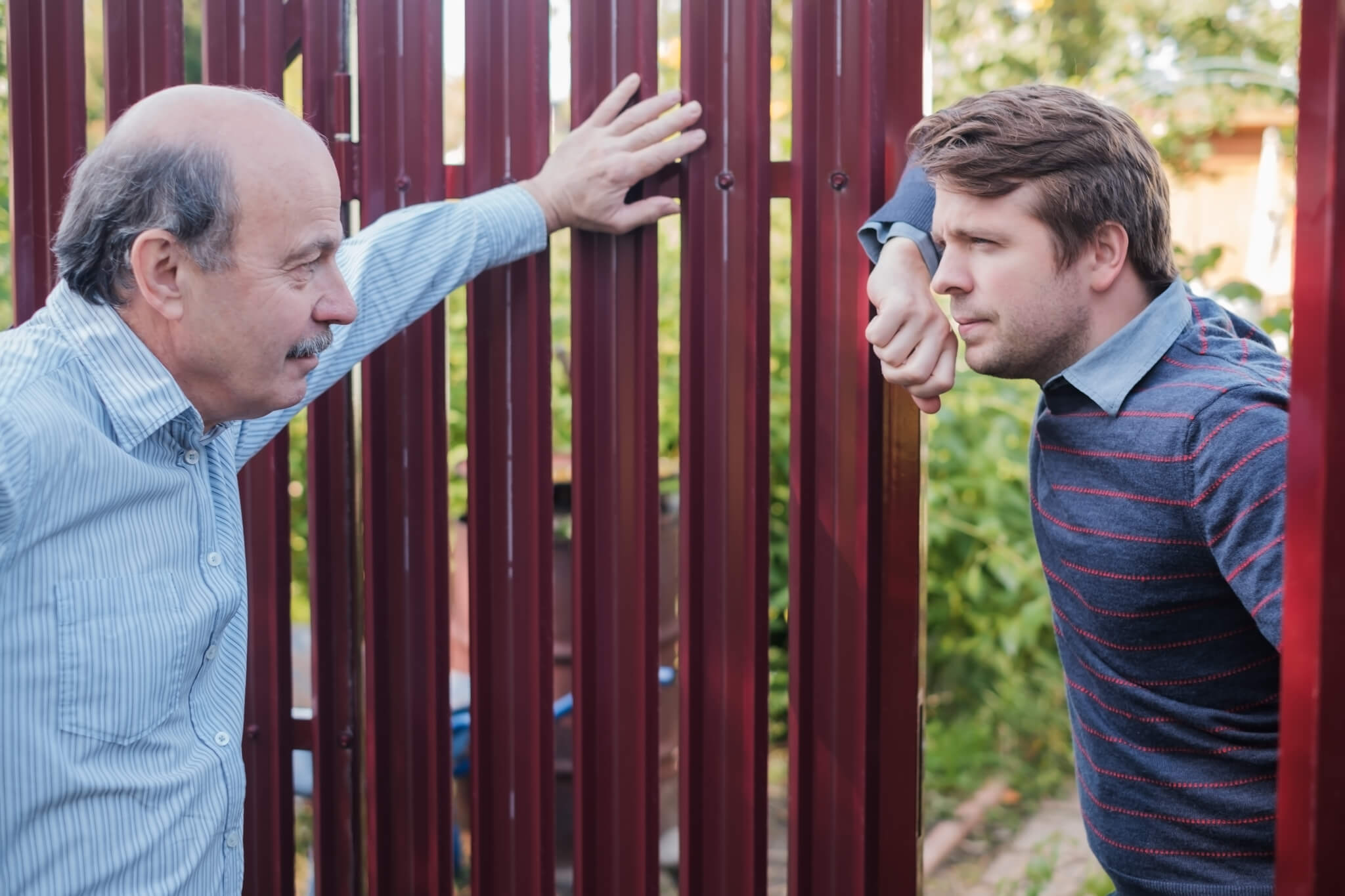 two neighbors talking through fence gate