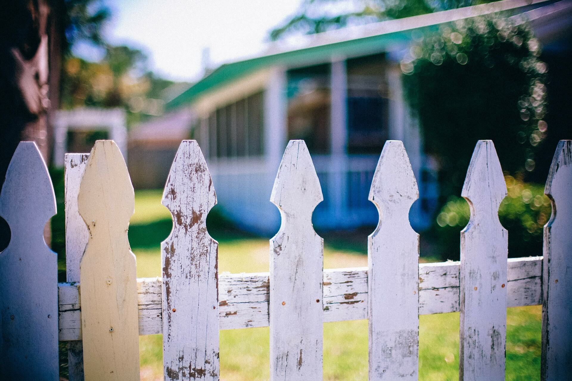 weathered white picket fence in front of house