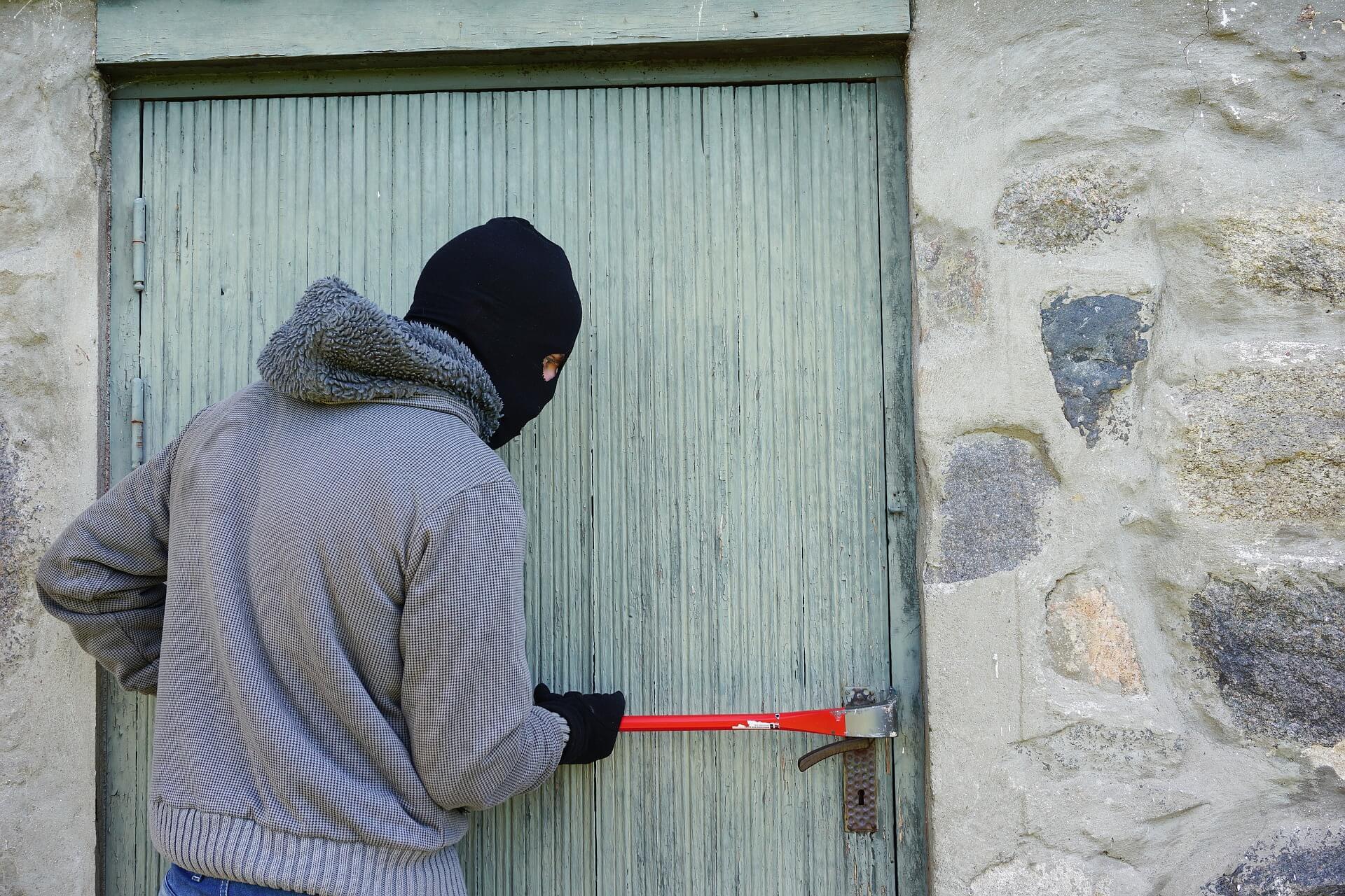 burglar breaking lock with crowbar