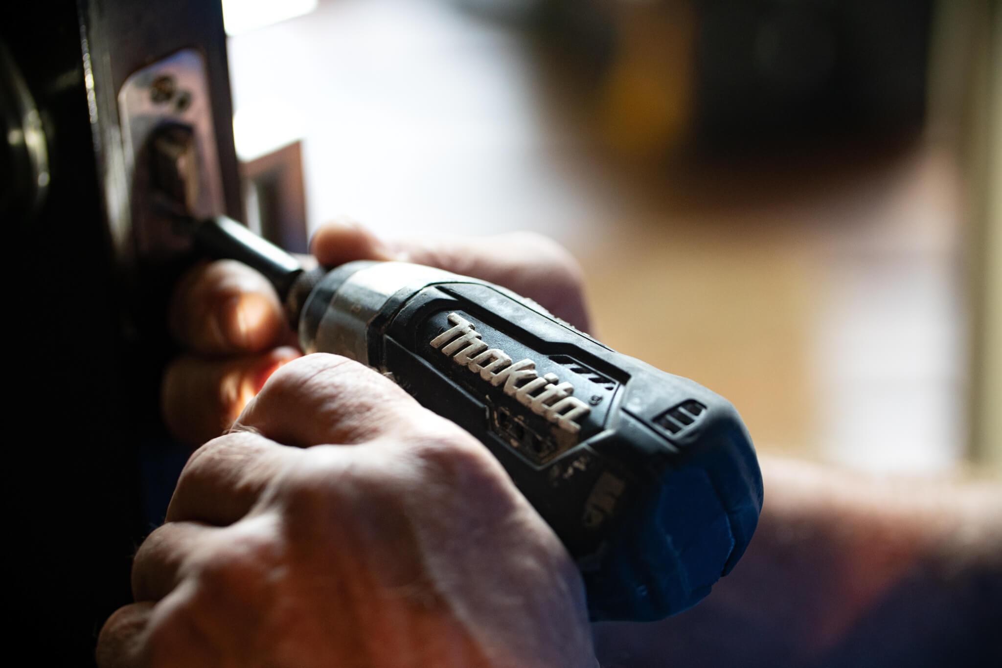 hand using power drill on door latch
