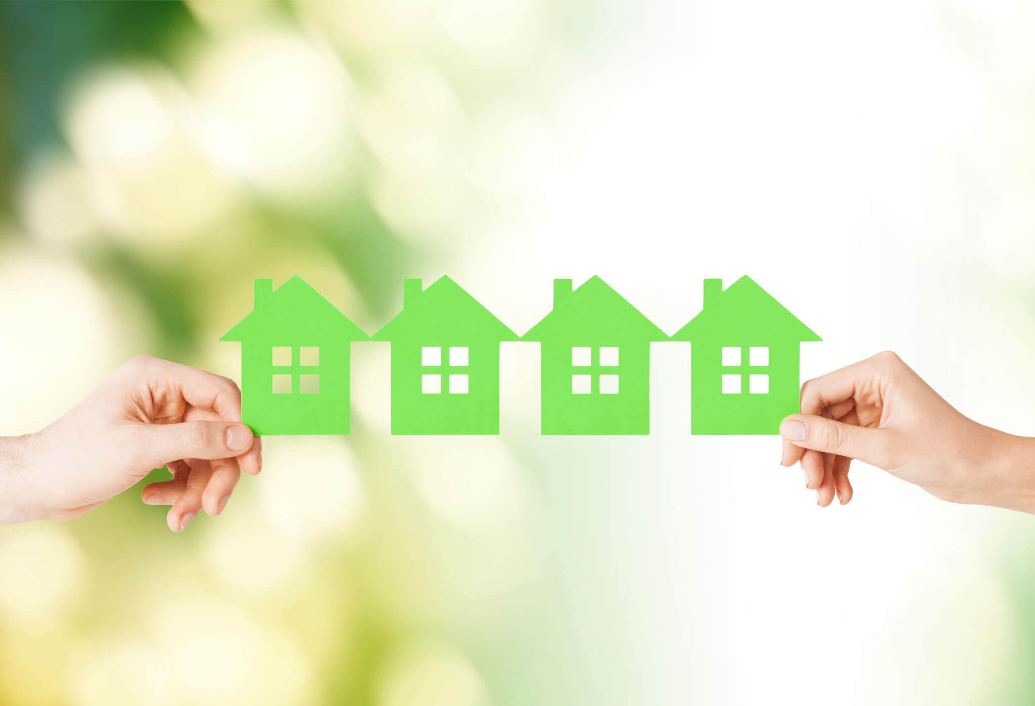 hands holding paper chain of green houses