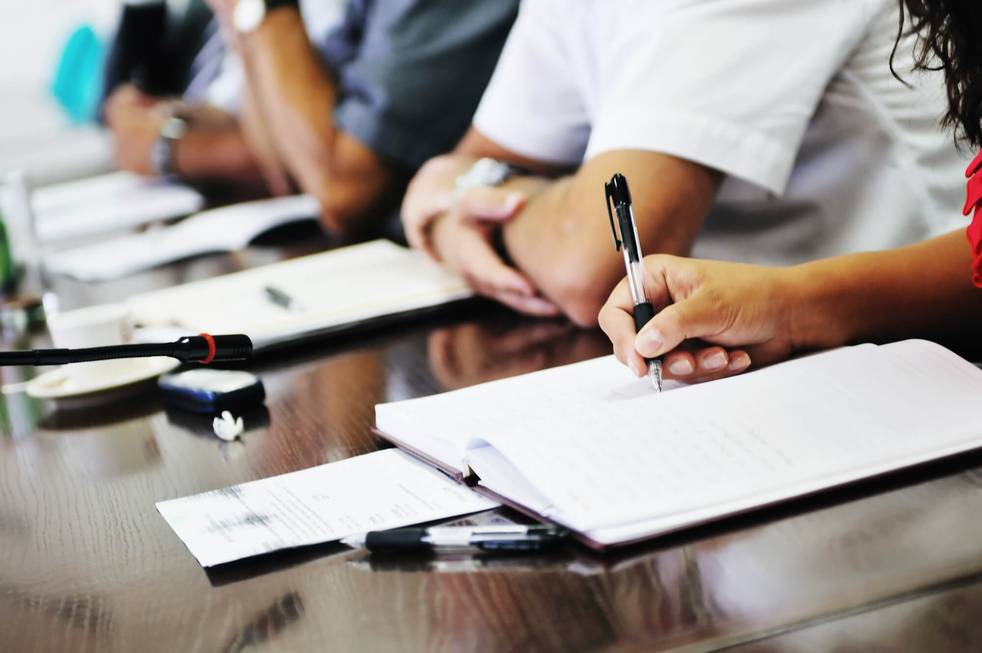 person taking notes during a meeting
