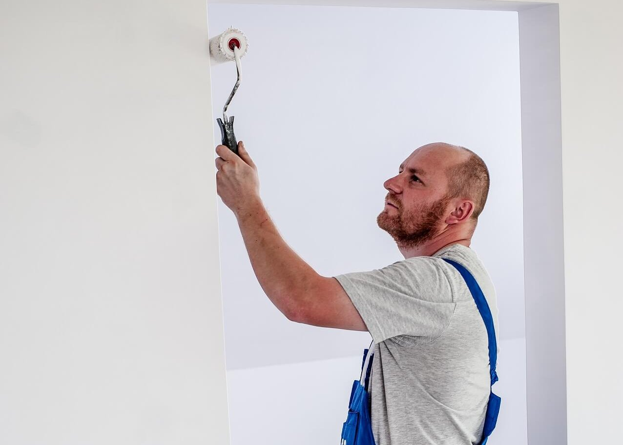man painting wall in empty room