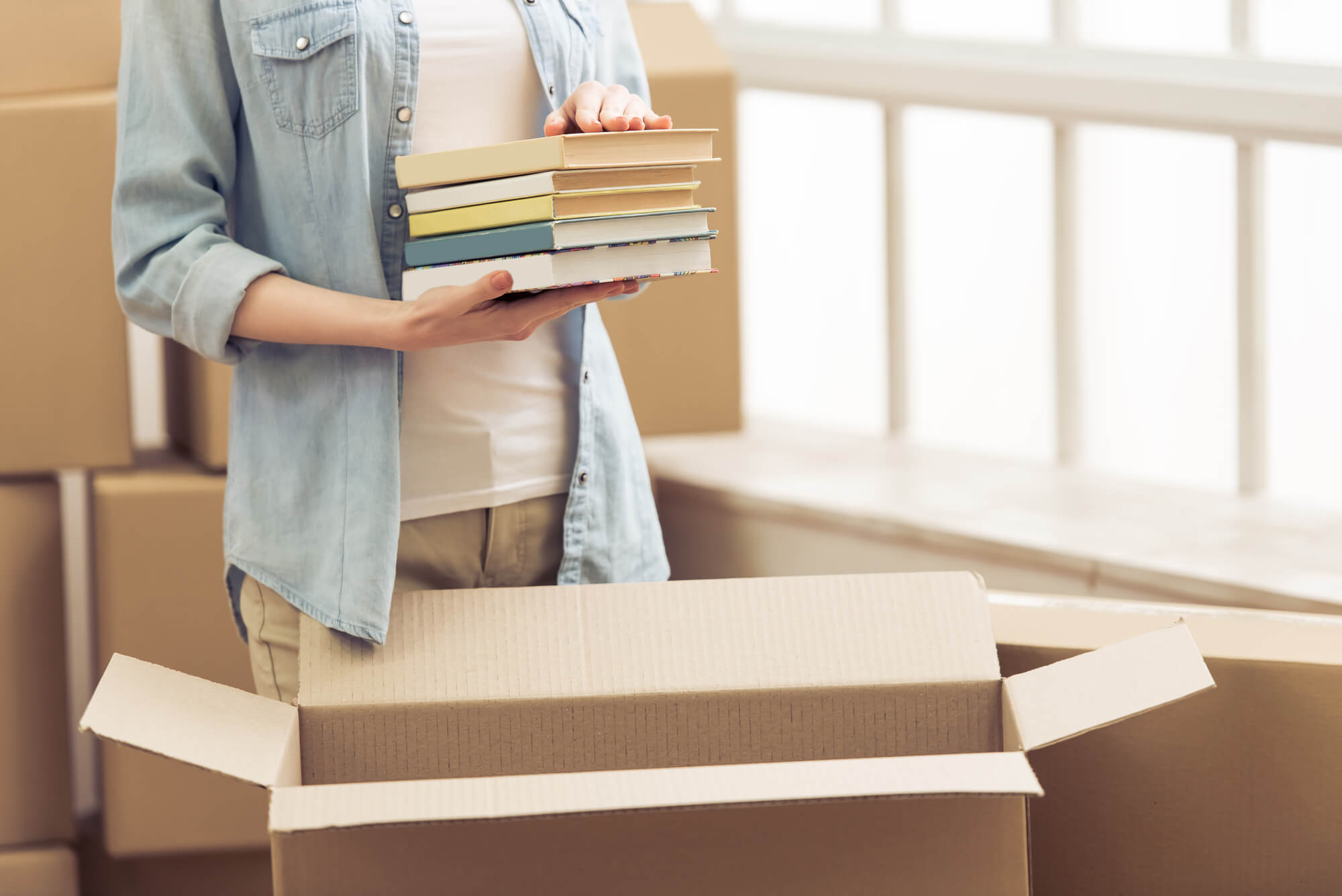 young woman packing books into a box
