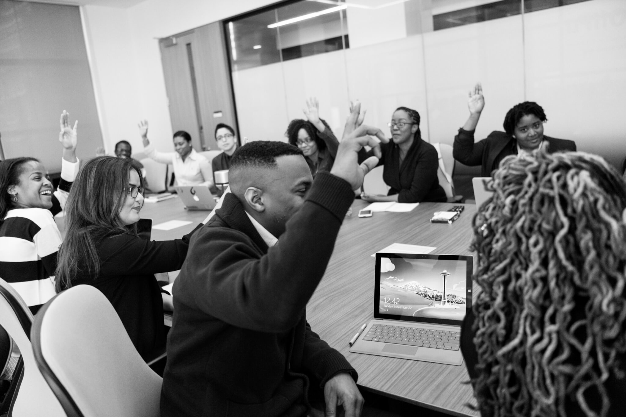 board members raising hands at a meeting